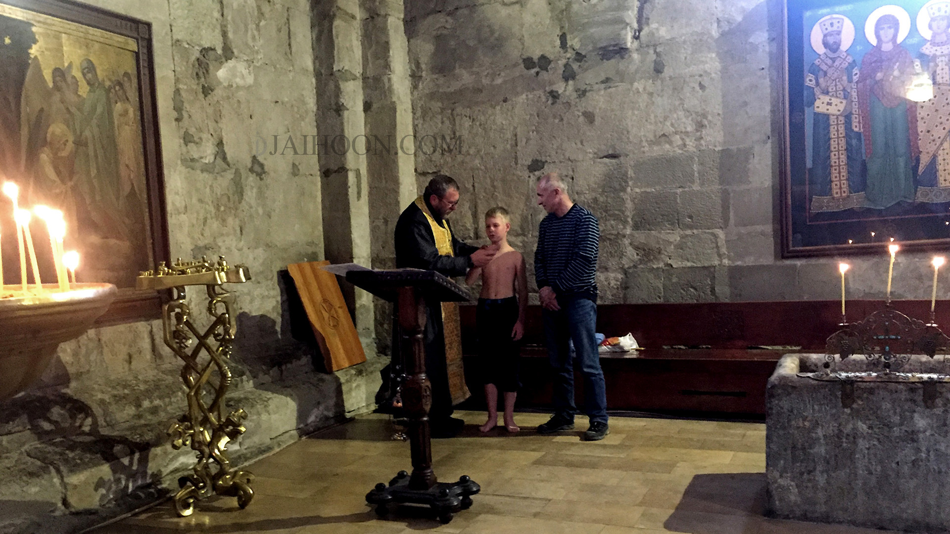A boy being baptized inside Svetitskhoveli Cathedral