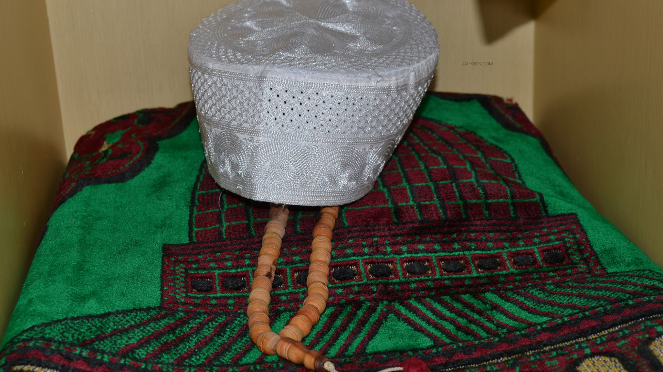 Prayer rug, cap and rosary inside hotel in Urumqi