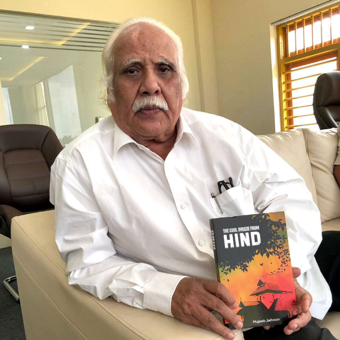 KKN Kurup holding The Cool Breeze From Hind, historical fiction by Mujeeb Jaihoon