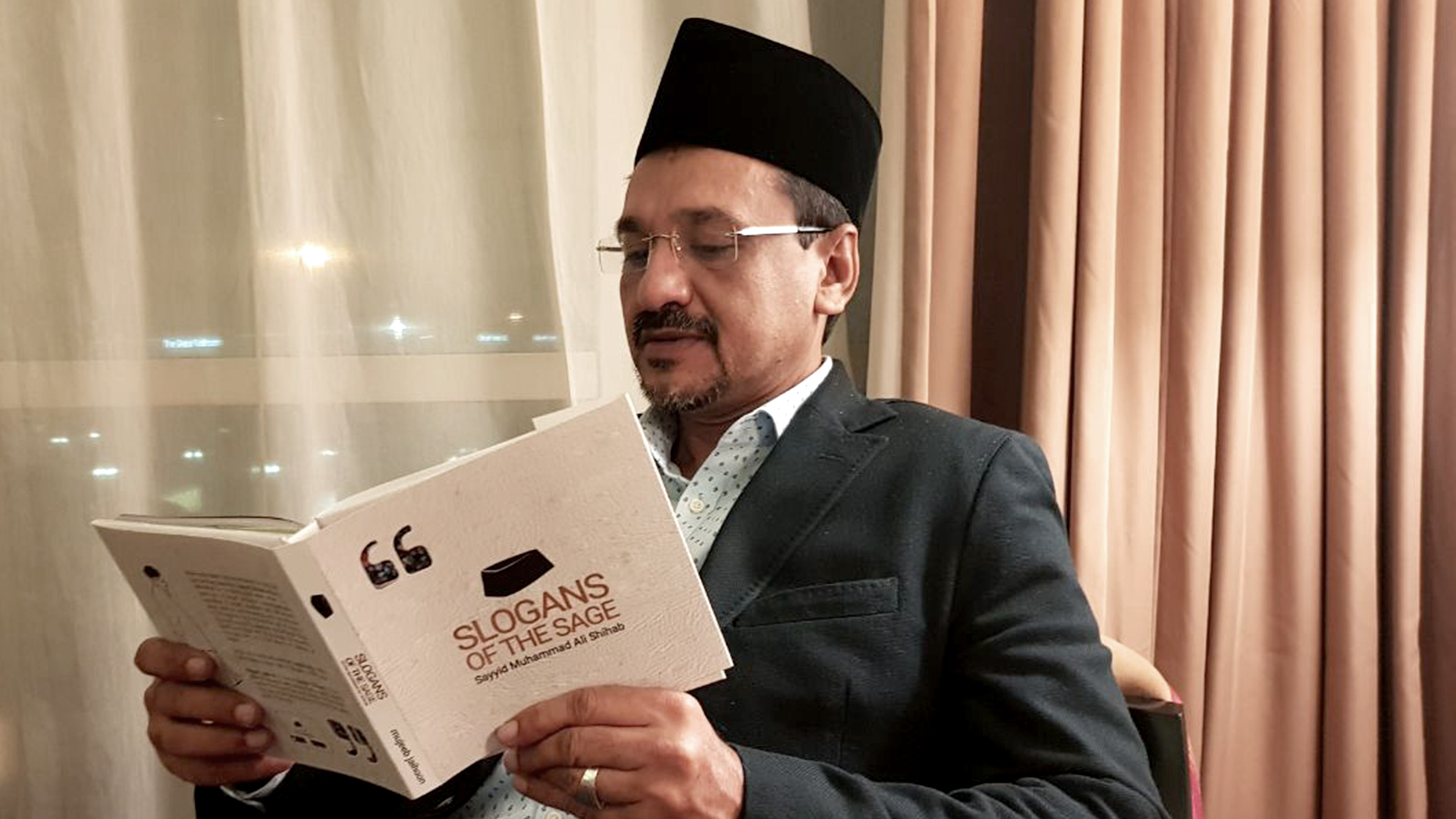 Panakkad Sayyid Sadik Ali Shihab Thangal, brother of Sayyid Shihab, absorbed in reading Slogans of the Sage by Mujeeb Jaihoon