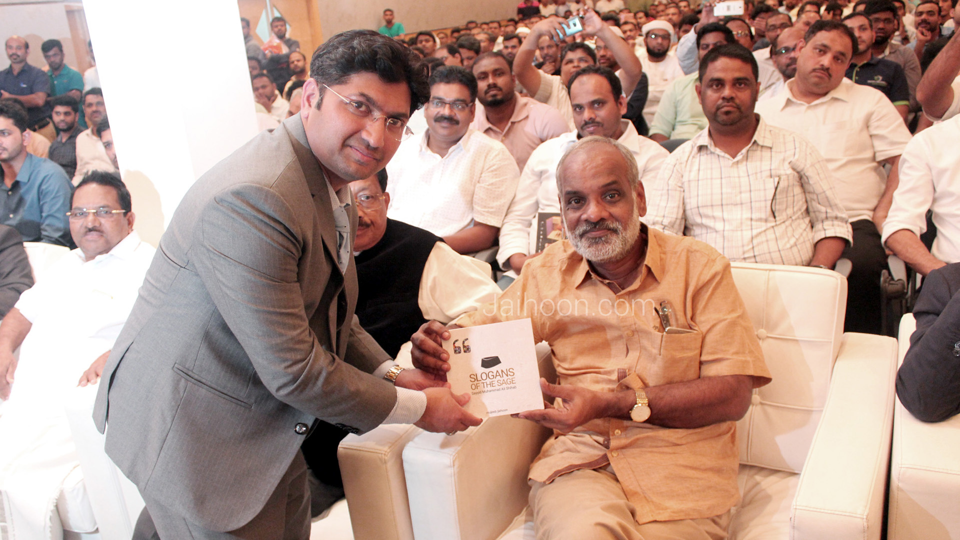 Presenting a copy of the book, Slogans of the Sage, to P. Surendran, award-winning Malayalam writer
